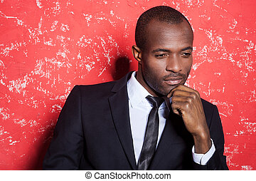 Lost in thoughts. Thoughtful young African man in formalwear holding hand on chin and looking away while sitting against red background