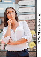 Lost in town. Thoughtful young woman standing near the directional sign and holding hand on chin