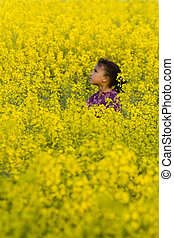 A beautiful mixed race girl looks skyward while surrounded by a field of yellow flowers