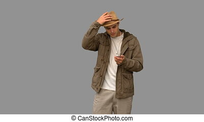 Lost man using his compass on grey screen in slow motion