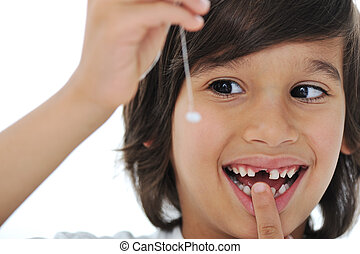 Lost milk-tooth, cute boy with long hair holding his tooth...