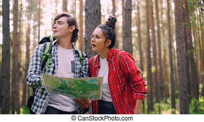 Lost tourists are standing in forest looking at map, talking...