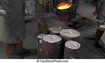 Lost wax bronze casting - filling the molds with the molten...