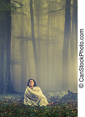 Lost woman in a dark misty forest