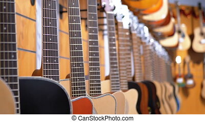 Lot of Acoustic Guitars Hanging in a Music Store. Shop...