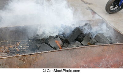 Lot of big coals lie on the brazier and smoke - A lot of big...