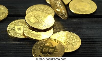 Lot of bitcoin coins falls on the wooden surface. Close up