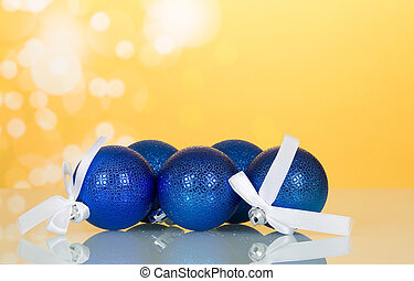 Lot of blue Christmas toys-balls with white ribbon, on yellow background