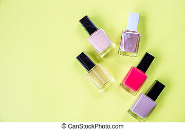 lot of bottles nail polish on yellow background top view. hands care concept with nail polish yellow desk background top view mock-up.Copy space