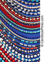 Lot of colored beads from different minerals and stone blue background