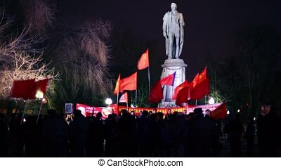 Lot of communists stand with flag in front of monument at...