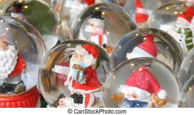 Lot of decorative snow globe or Christmas balls with Santa Claus inside. Christmas and New Year's decor for the home on the counter of the Christmas market