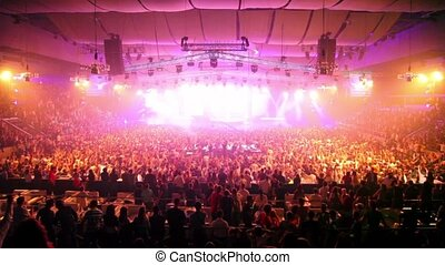 Lot of fans at rave party, dj rises hands on stage