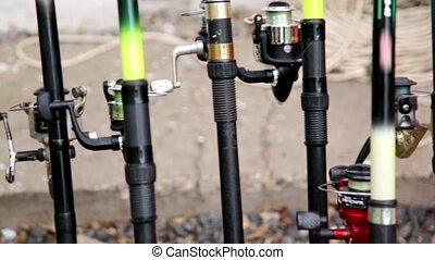 Lot of fishing rods stand near wall, closeup view in motion