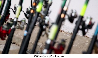 Lot of fishing rods stand near wall, focus changes