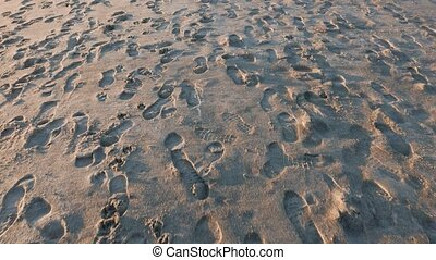 lot of footprints in the sand at sunset