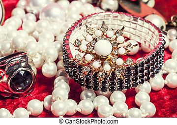 lot of jewellery close up in red velvet box, ring bracelet with perl