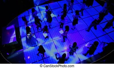 Lot of kids dance at discotheque in dark club, view from above