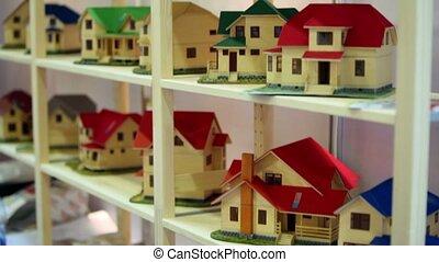 Lot of models of houses on wooden shelves, upward motion