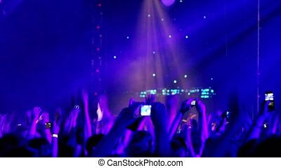 Lot of people at rave party, view from behind, hands and heads, displays of photo cameras
