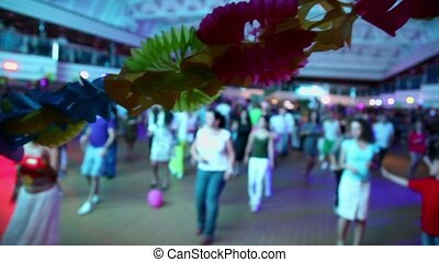 Lot of people dance in hall, focus on garland of paper flowers