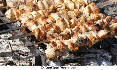 Lot of pieces of meat on skewers are roasted on a bonfire. A...