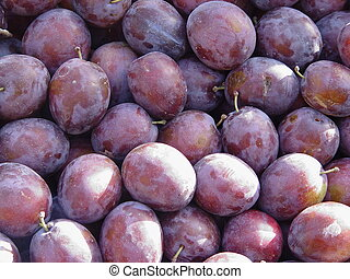 lot of plums on a market