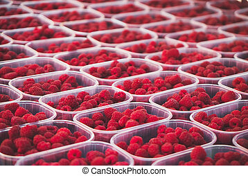 Lot of ripe red raspberries in the supermarket.