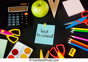 lot of school supplies, and in the center  the composition  note with the words - back to
