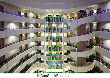 Lot of stories in large hotel, spiral staircase connects all floors; green ivy growing on balconies