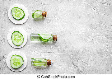 Lotion with cucumber pattern. Grey background top view copyspace