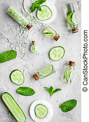 Lotion with cucumber pattern. Grey background top view