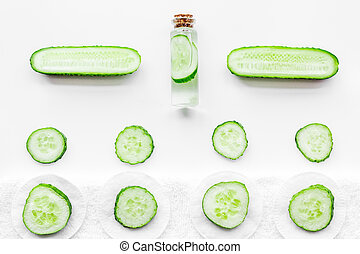 Lotion with cucumber pattern. White background top view