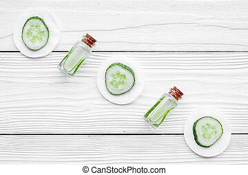 Lotion with cucumber pattern. White wooden background top view copyspace