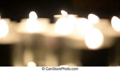 Lots of candles burning in the dark. Defocusing. White light, bokeh