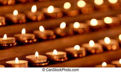 Lots of candles with shallow depth. Small candles on table in Catholic Church.