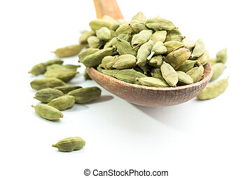 Lots of cardamom pods on wooden spoon