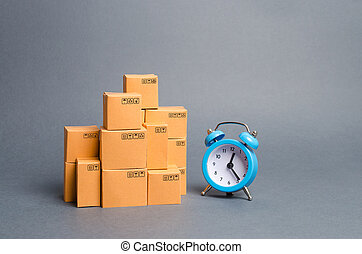 Lots of cardboard boxes and a blue alarm clock. Express delivery concept. Temporary storage, limited offer and discount. Optimization of logistics and delivery, improving transportation efficiency