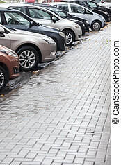 lots of cars parking in city street on rainy day