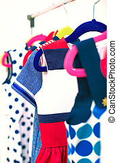 Lots of colorful dresses on hangers in shop.