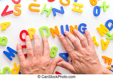 lots of colorful letters on a table, hands forming german ...