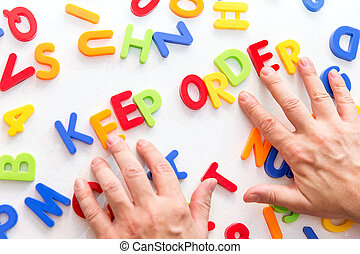 lots of colorful letters on a table, hands forming text, ...