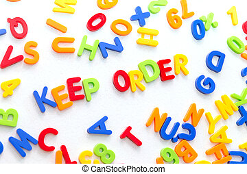 lots of colorful letters on a table, text keep order in the ...