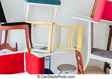 lots of different chairs in the interior of an empty white room
