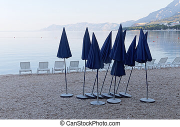 Lots of empty deck chair and many parasol