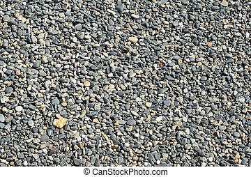 Lots of gray beach stones close up.
