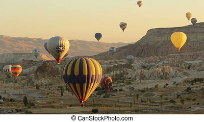 Lots of hot air balloons flying over valleys in Goreme, Cappadocia, Turkey.