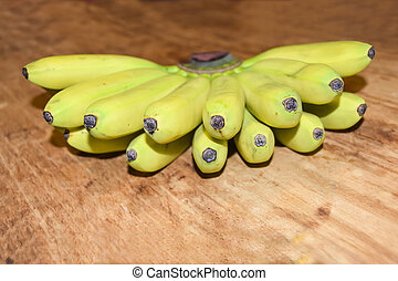 mini bananas on a wooden background