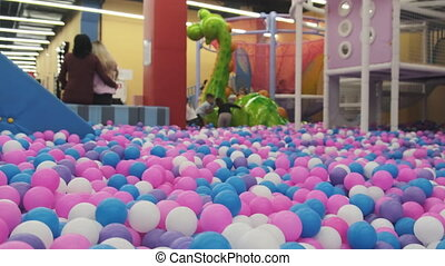 Multi-colored Balls in the Children's Entertainment Center. Lots of colored plastic balls in a playground ball pool. Game center for a family weekend. Pool with bright balls background. Indoor games.