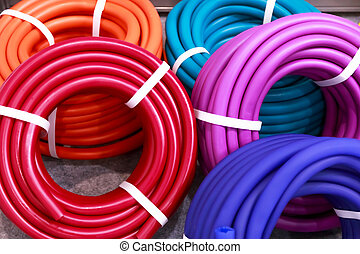 Lots of new multicolored coils of polymer hoses for watering, garden goods and tools in stock on display case for sale